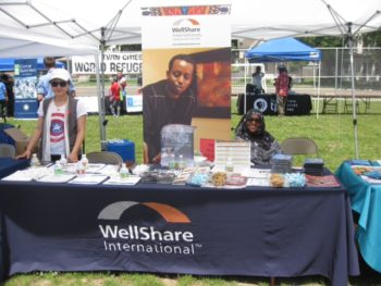 Tha Dha and Adar manage WellShare's information table at the Twin Cities Refugee Day celebration.