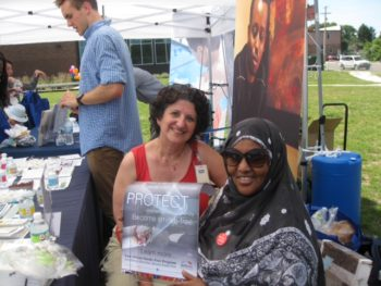 Eugenia and Adar showing off the East African Smoke-Free Program's secondhand smoke poster.
