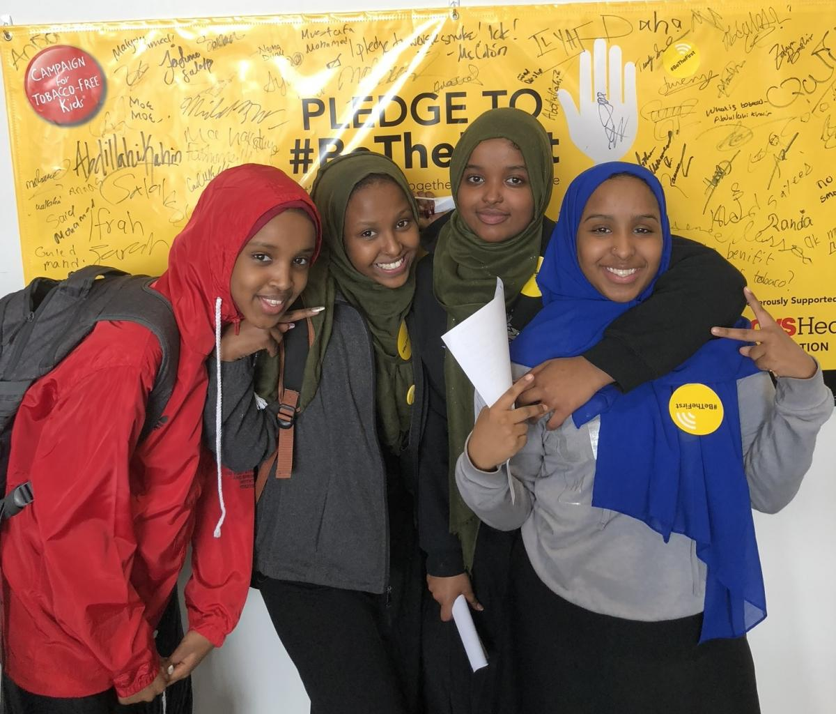 girls smiling in front of pledge wall